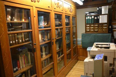 Die Bücherregale aus der Gründungszeit mit Glasscheiben und Ornamenten, die sich im Obergeschoss der Bücherei wiederholen