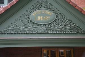 Liebevoll geschnitztes Eingangsschild der Public Library in Mystic