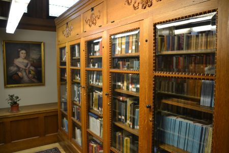 In den alten Regalen mit den Glasscheiben davor stehen auch alte Buchschätzchen. Hinten am Ende kann man den Rahmen eines Gemäldes erkennen, das da hängt