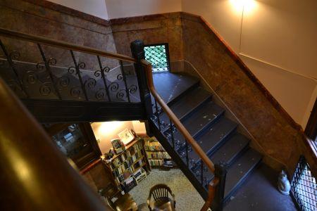 Das Treppenhaus. Auch hier finden sich Porträts an den Wänden und mindestens eine Katzenskulptur auf einem Treppenabsatz