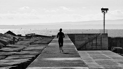 """Joggerin vor Meeresküste passenzu """"Laufen"""" von Isabel Bogdan"""