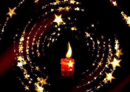 Kerze schimmert mit Strenen im Dunkeln - Weihnachten