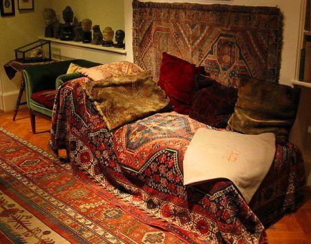 Die Couch aus dem Arbeitszimmer von Sigmund Freud - viele rote Teppiche auf der Couch und drumherum auf dem Boden und an der Wand