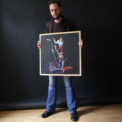 Ein Mann hält ein Bild von sich und einem Kind hoch. Auf dem hoch gehaltenen Bild sitzt das Kind auf seiner Schulter. Neben ihm steht ein roter Staubsauger.