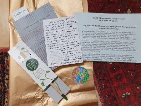 Der Inhalte vom Lyrik-Abonnment nach dem Auspacken: goldenes Geschenkpapaier, darauf der graue Band, der Bleistift in eienr Pappmanschette, die handgeschriebene Karte und der Zettel mit der Einführung.
