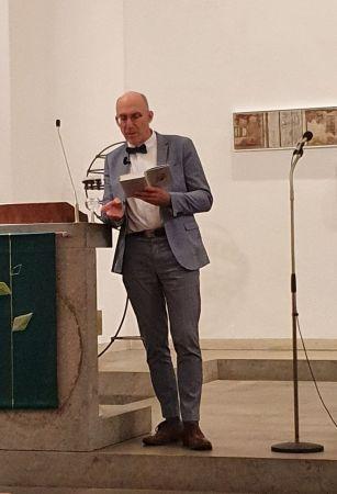 Ewald Arenz, Mann in grauem Anzug, mit Glatze, leht an Kanzel mit grünem Antependium, neben ihm ein Mikrofon, hinter ihm Bilder einer Ausstellung in der Christuskirche in Köln-Dellbrück
