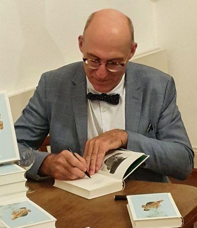 """Ewald Arenz signiert mit seinem Füller Exemplare von """"Der große Sommer"""". Mann im gruen Jackett, mit Glatze udn schwarzer Fliege und einer Brille."""